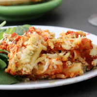 close-up of vegan baked ziti on a plate with green salad