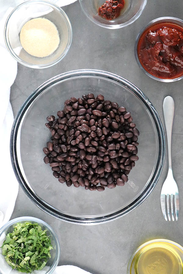mixing bowl of black beans surrounded by small bowls of bean dip ingredients