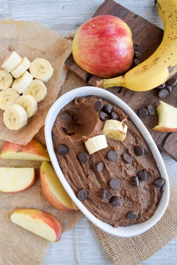 overhead photo of vegan chocoalte peanut butter hummus in a serving bowl next to apples and bananas