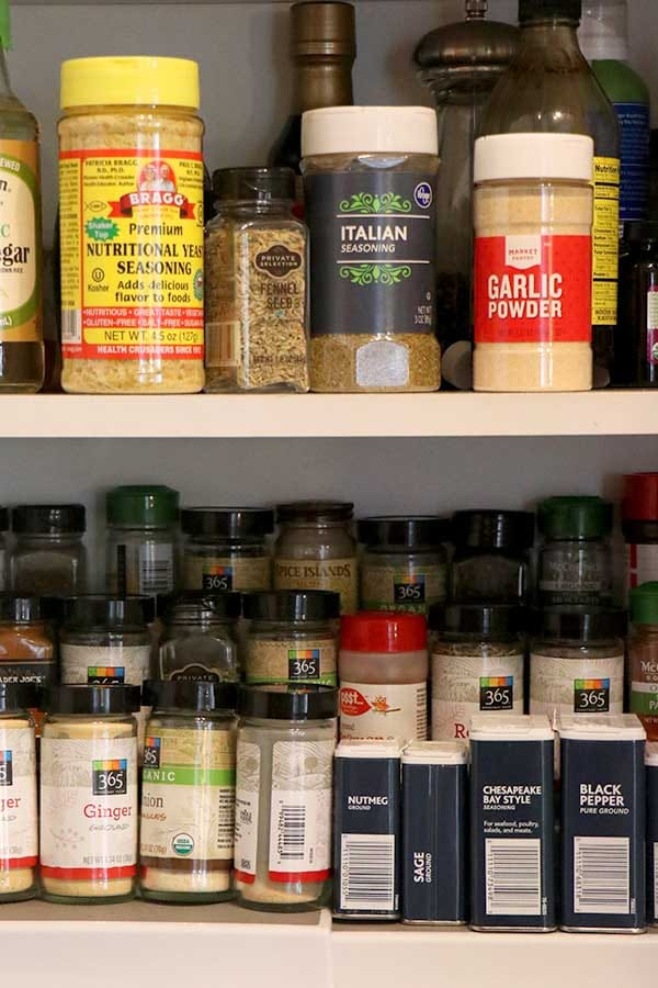 spice cabinet with bottles, jars, and tins of various herbs and spices