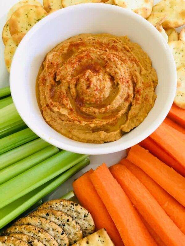close-up of peanut butter hummus in the middle of a veggie tray with celery sticks, carrots, and crackers