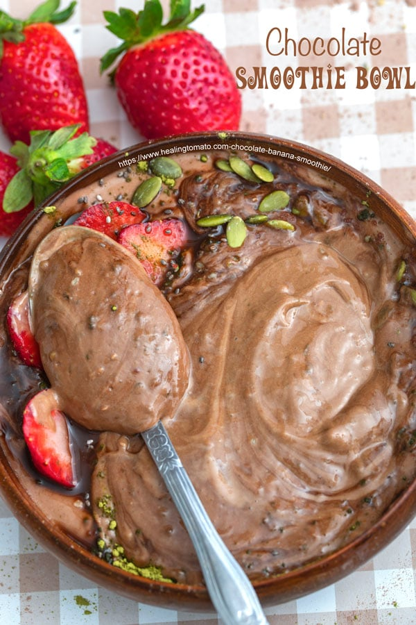 overhead photo of a vegan peanut butter smoothie bowl with a spoon and sliced strawberries