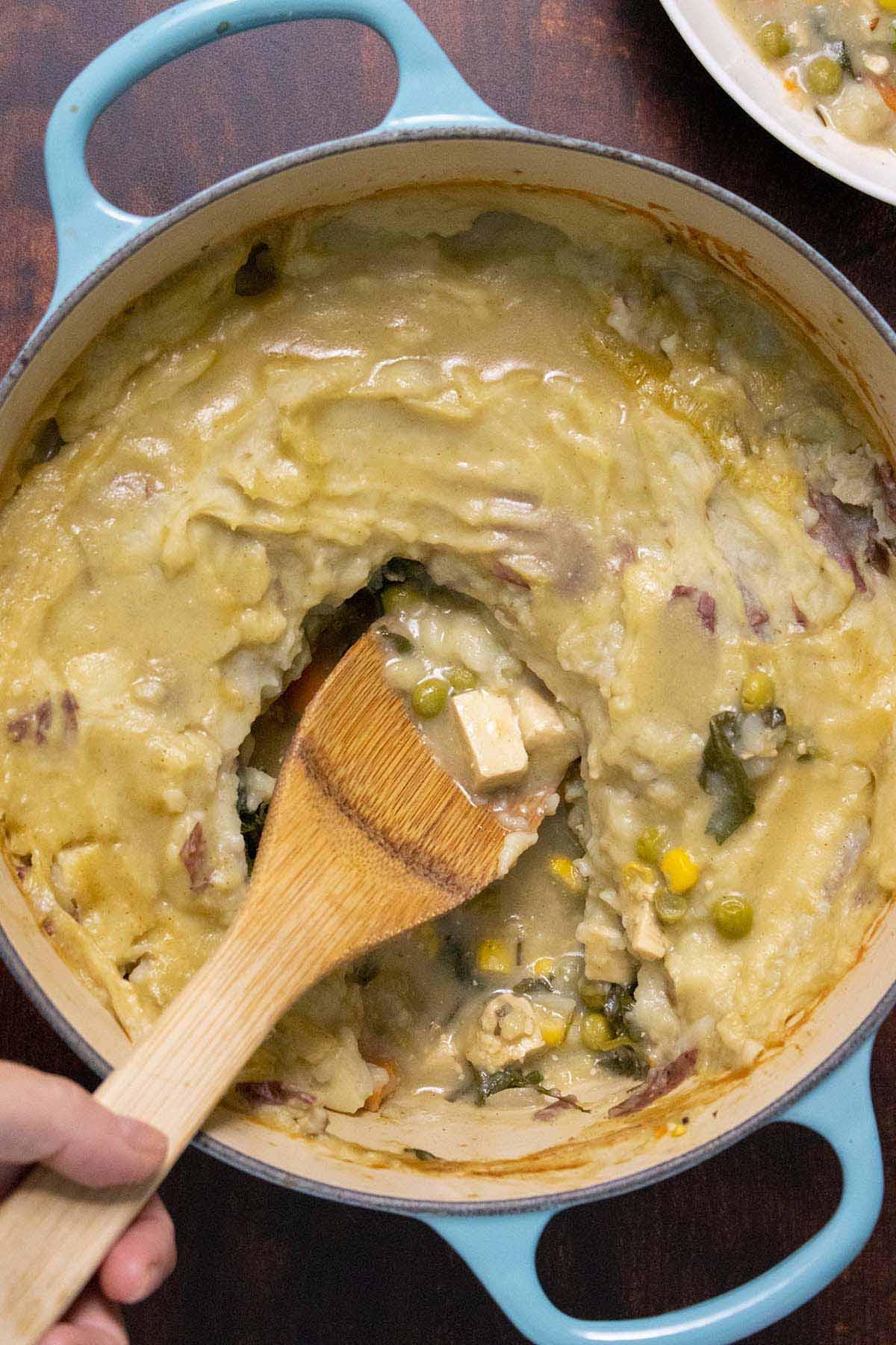 Dutch oven full of vegan shepherd's pie with tofu on the serving spoon
