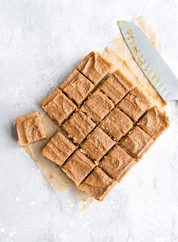 overhead photo of peanut butter blondies cut up on a piece of parchment paper next to a knife