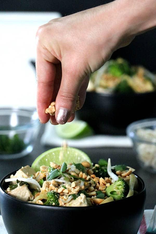 Sprinkling peanuts onto a bowl of vegan pad thai