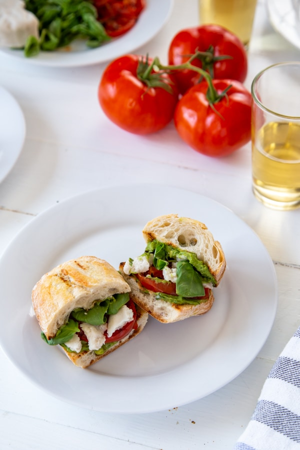 vegan caprese sandwiches on a white plate on a white tabletop