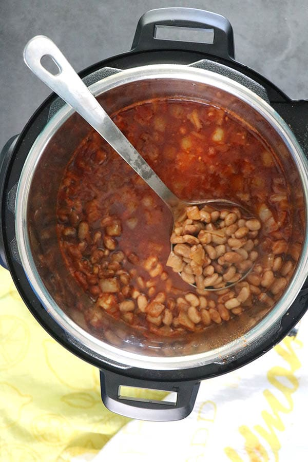 serving pinto beans with a ladle from the Instant Pot