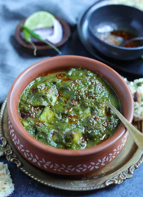 saag aloo in a brown bowl with a spoon