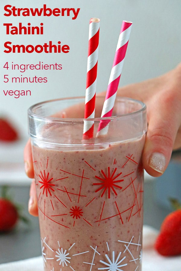hand picking up a strawberry tahini smoothie in a glass with two straws