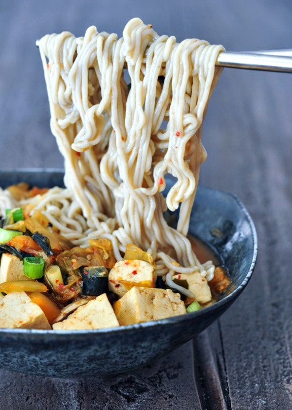 bowl of kimchi noodle soup with tofu and veggies