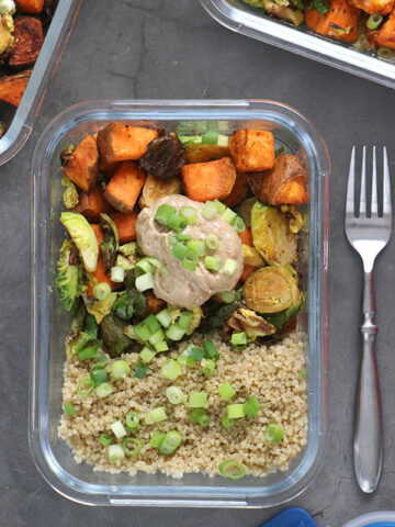 meal prep container with sweet potato, quinoa, brussels sprouts, and creamy sauce