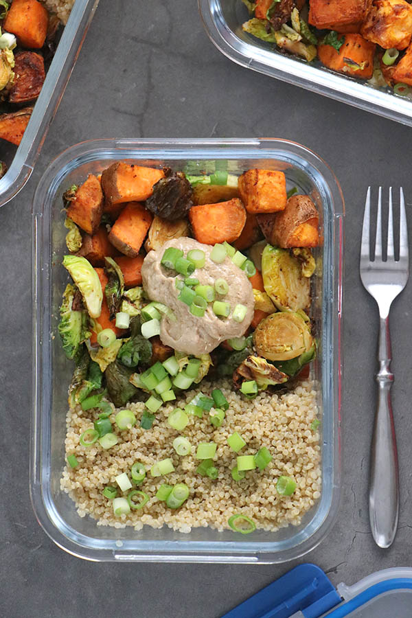 Quinoa and vegetables in a meal prep container with tahini sauce on top