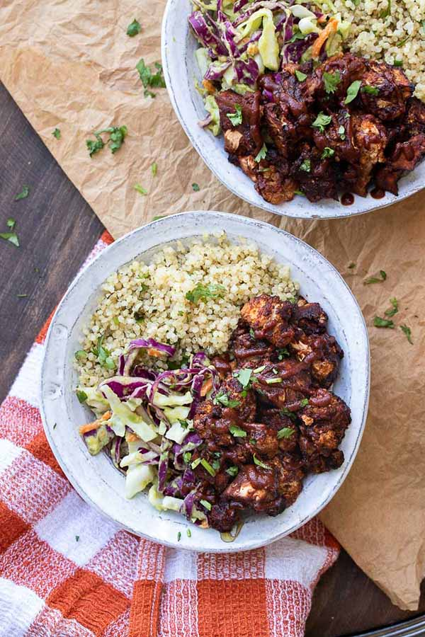 bowls of bbq cauliflower with quinoa and red cabbage avocado slaw