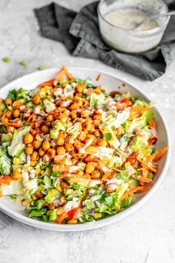 white bowl of bbq chickpea salad on a marble tabletop