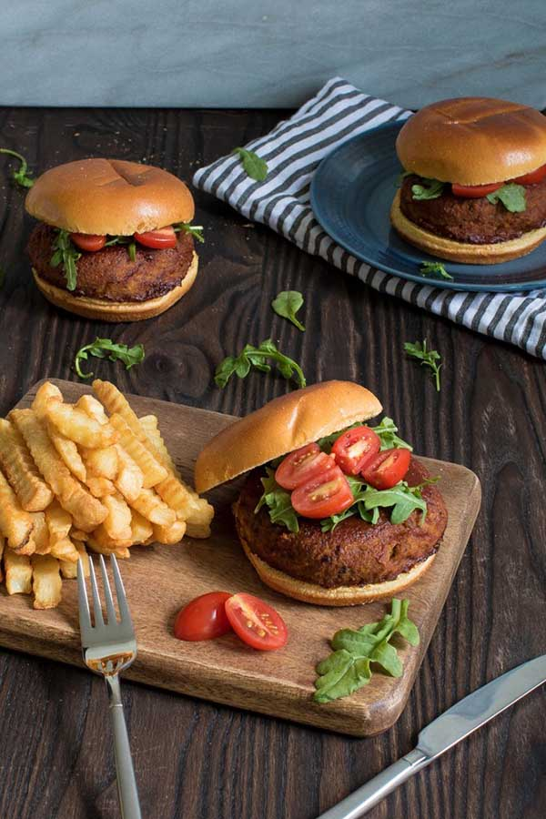 lentil burgers on a wooden table with french fries