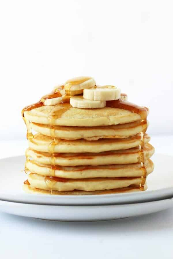 stack of vegan pancakes topped with banana slices and maple syrup on a white plate with a white background