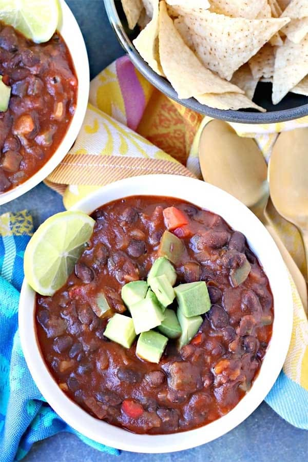 bowls of black bean chili with chips to dip