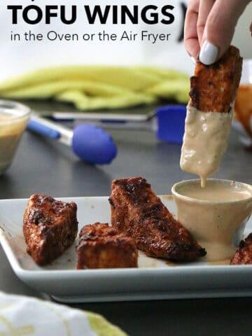 A person dipping a BBQ tofu wing into a ramekin of tahini sauce