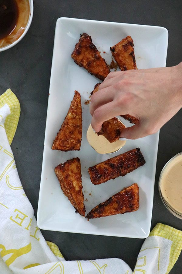 overhead photo of BBQ Tofu Wings on a white serving tray. Hand dipping one into tahini sauce