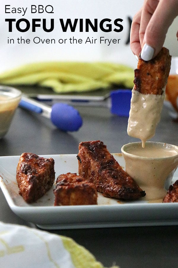 A person dipping a BBQ tofu wing into a ramekin of tahini sauce