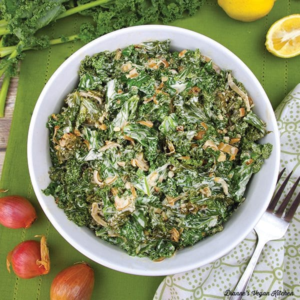 white bowl of creamed kale on a green tabletop