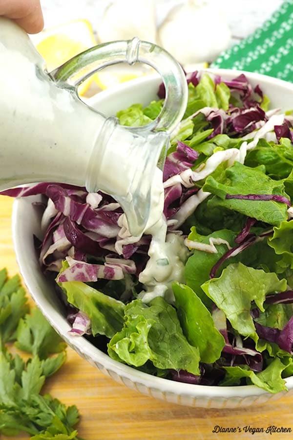 pouring vegan buttermilk dressing onto a bowl of easy vegan green salad