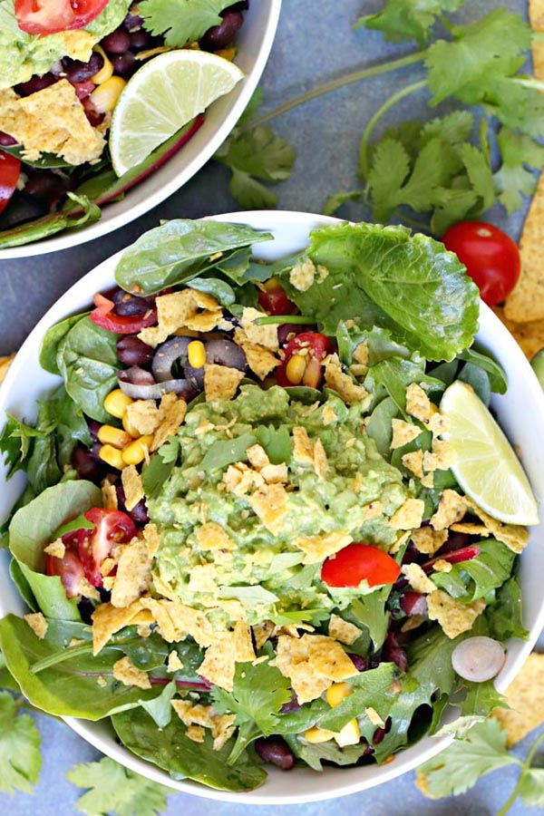 bowl of guacamole salad with veggies and tortilla chips