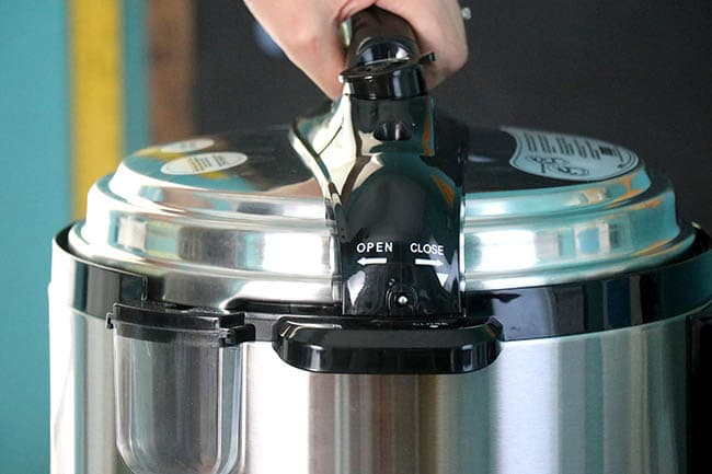 hand locking the lid of an electric pressure cooker