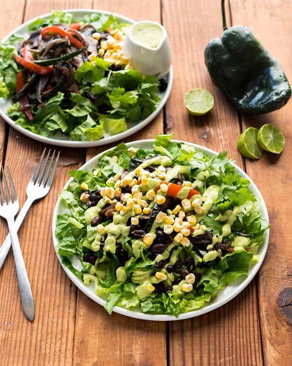 white plates of vegan fajita salad on a wooden table