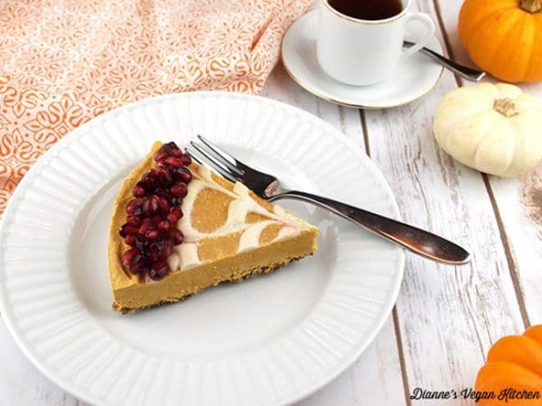 pumpkin swirl cheesecake topped with pomegranate seeds on a white plate