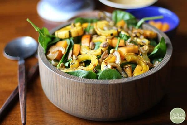 wooden bowl of vegan thanksgiving salad with squash and spinach
