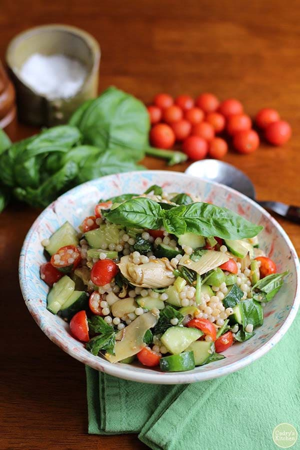 photo of Israeli couscous salad in a colorful bowl with ingredients on the table