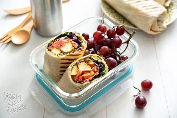 tofu rainbow wraps in a lunchbox with red grapes