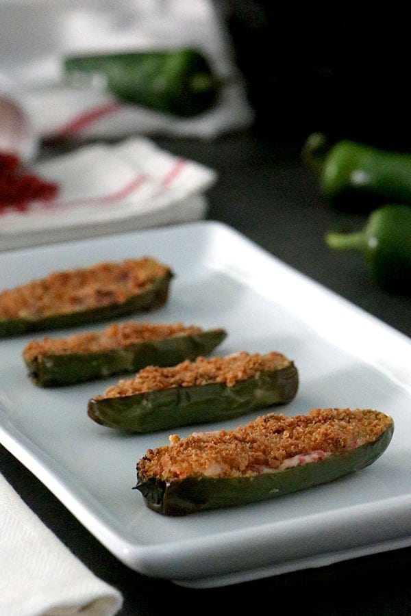 tray of stuffed jalapenos with bacon bits and jalapenos in the background