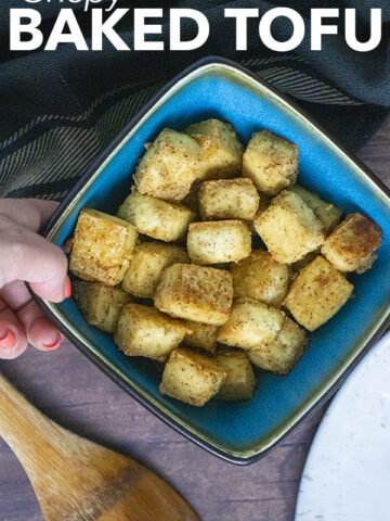 hand placing a bowl of crispy baked tofu onto a wooden table