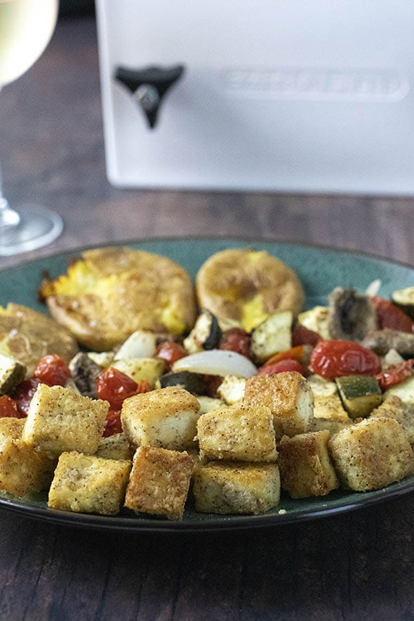 crispy tofu on a plate with vegetables and potatoes. EZ Tofu Press in the background