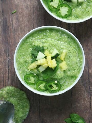 Pineapple gazpacho in a bowl topped with chopped fresh pineapple, cucumber, jalapeno, and cilantro