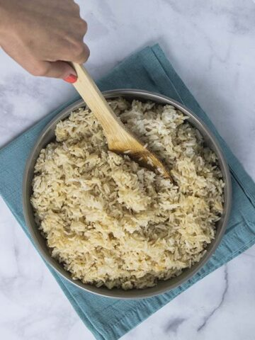 serving spoon dipping into a bowl of Instant Pot coconut rice