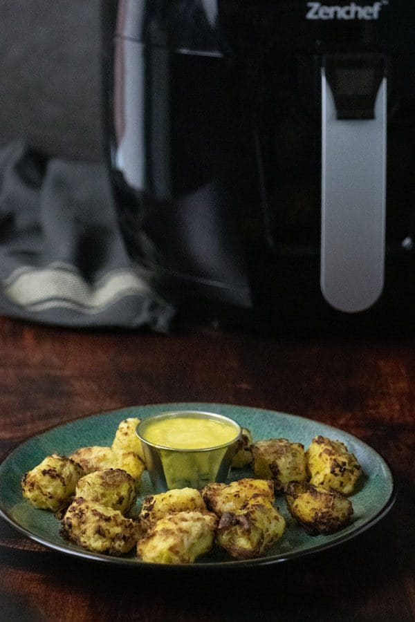plate of cauliflower tots with the air fryer in the background