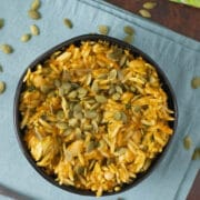 bowl of baked orzo garnished with pumpkin seeds