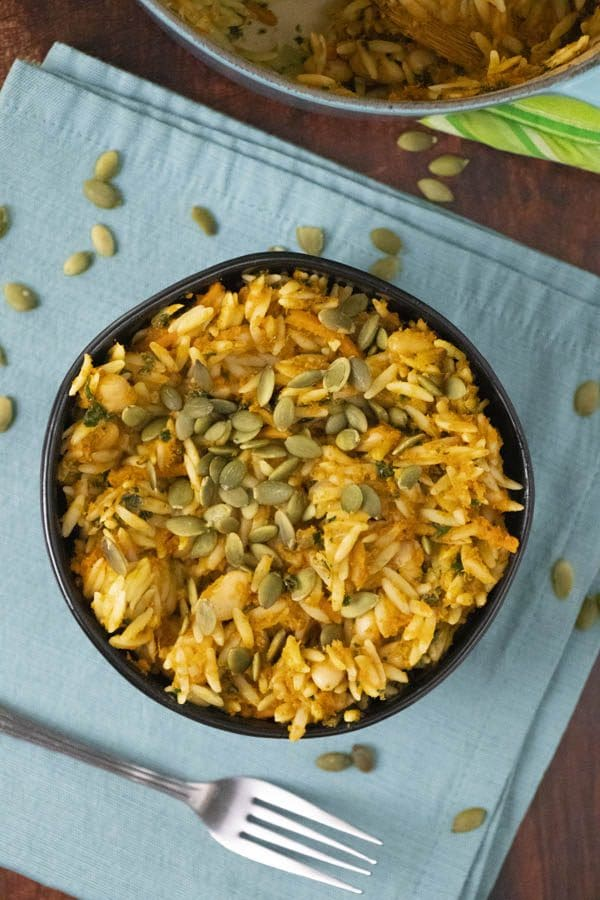 black bowl of pumpkin baked orzo on a blue napkin with pumpkin seeds scattered on top