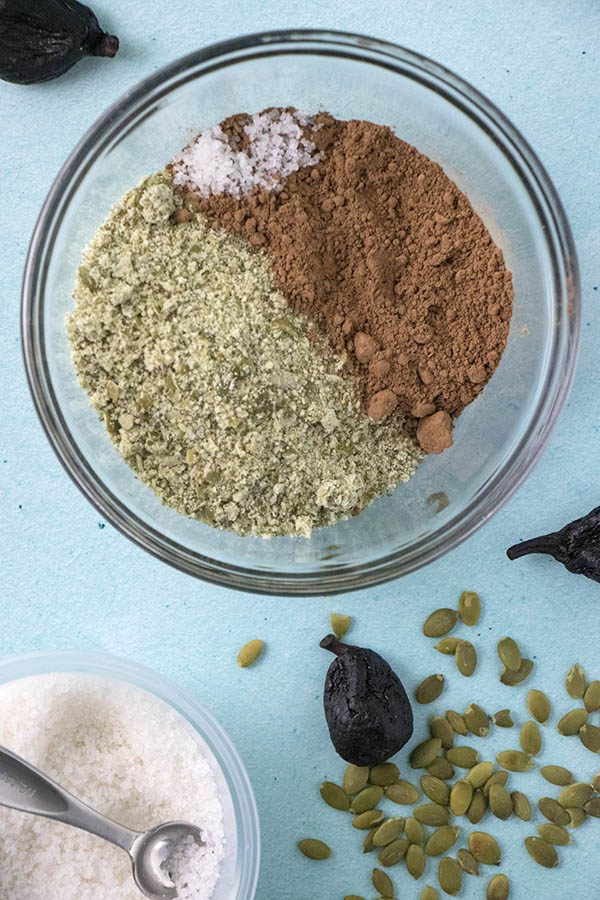 cocoa powder, sea salt, and pumpkin seed flour in a bowl with ingredients scattered on the table