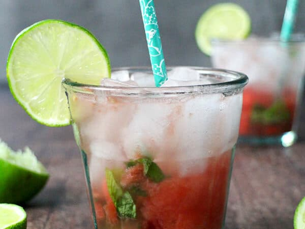 glass of watermelon smash with a blue straw and a wheel of lime for garnish