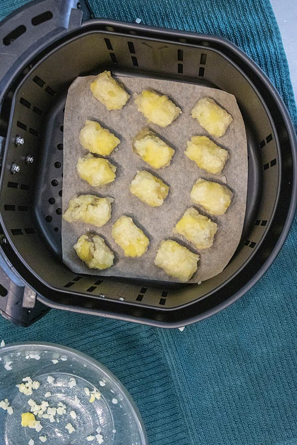 uncooked tots in an air fryer basket lined with parchment paper