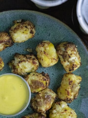 overhead photo of cauliflower tots on a blue plate with dipping sauce