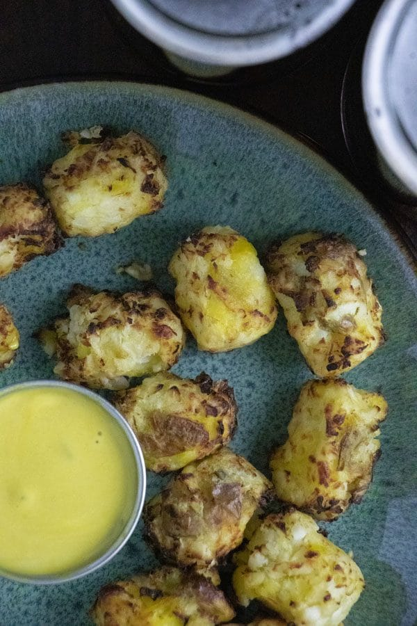 close-up of air fryer cauliflower tots with vegan honey mustard dipping sauce on a blue plate