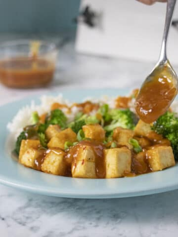 spooning sauce onto General Tso's tofu