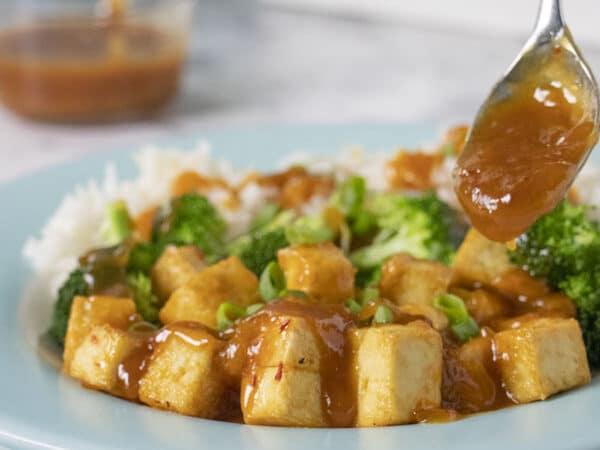 spooning sauce onto General Tso's tofu