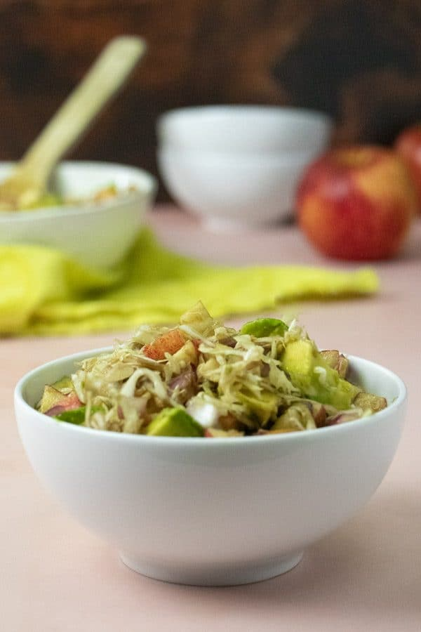 close-up of apple slaw in a bowl with serving dish in the background