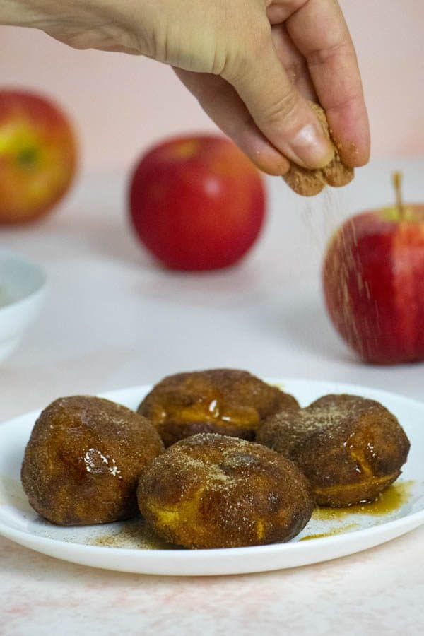 sprinkling cinnamon-sugar onto a plate of apple fritters